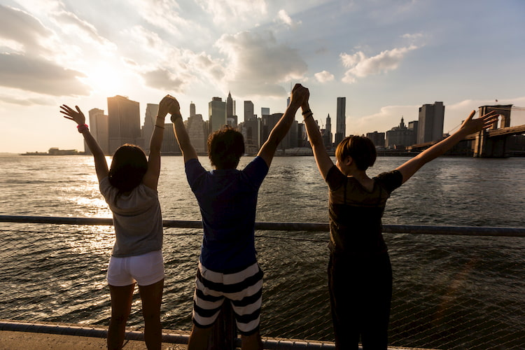 friends raise their arms as they look at the new york city skyline