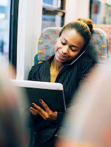 a business woman talks on the phone and works from a mobile tablet on an employee shuttle in NYC