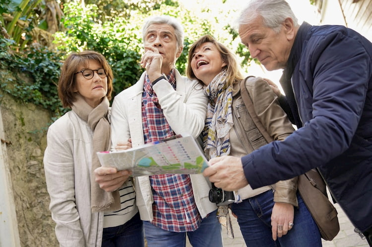 a group of senior citizens consult a map as they walk around New York City