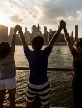 friends excitedly raise their hands as they look at the new york city skyline